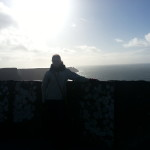 Standing at the railing of the Cliffs of Moher.