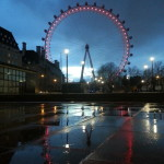The London Eye lit up on a rainy evening.