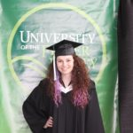 Gotta love the cap and gown look, standing in front of my school colours and logo!
